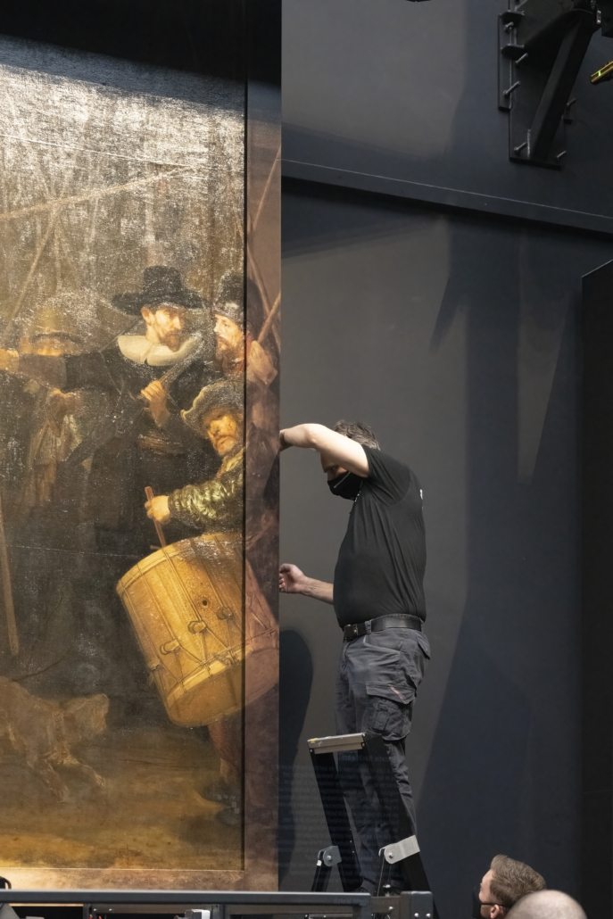 Rijksmuseum attendants install a narrow strip to the right side of Rembrandt's 'Night Watch' that recreates a section trimmed off decades later. Photo credit: Rijksmuseum/Reinier Gerritsen
