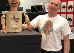 Steve Slotin poses with a ventriloquist's dummy that was being auctioned by Slotin Folk Art Auction. His wife Amy joked that it looked like Steve's twin, prompting his bemused expression.