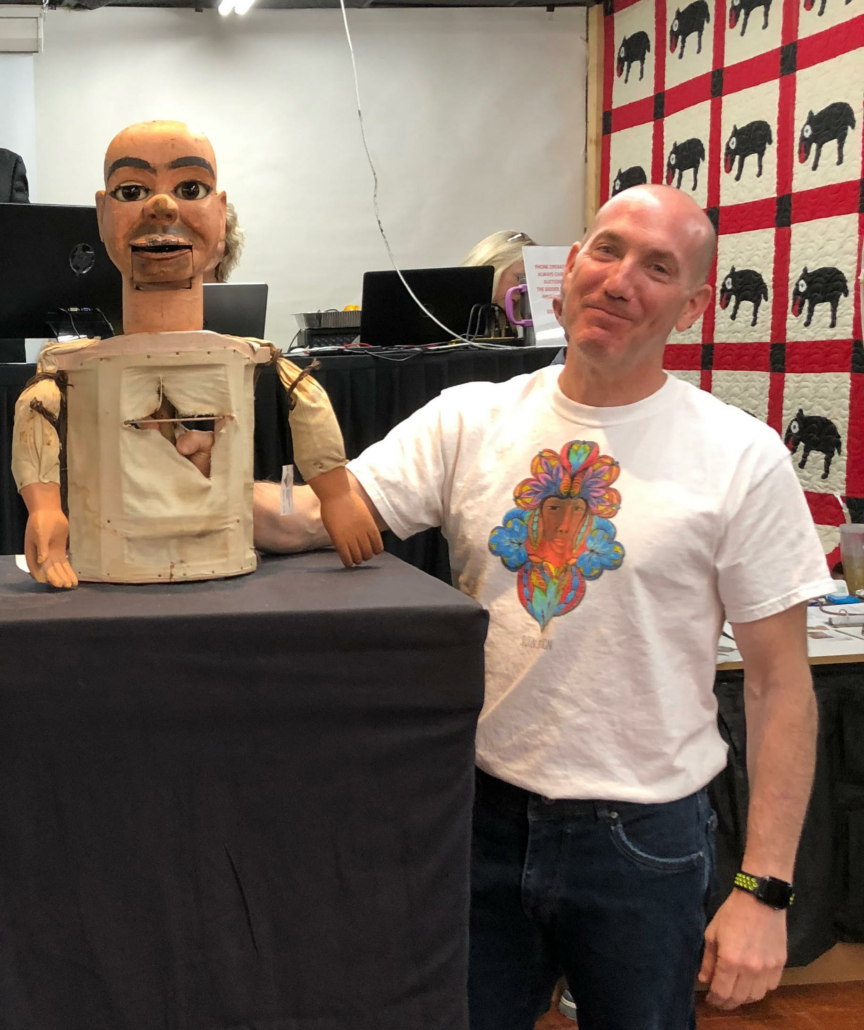 """Steve Slotin poses with a ventriloquist's dummy that was being auctioned by Slotin Folk Art Auction. His wife Amy joked that it looked like Steve's twin, prompting his """"I'm not amused"""" expression."""