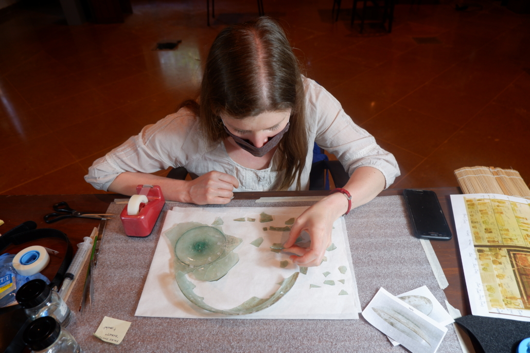 """Conservator Claire Cuyaubere assisting with """"puzzle-work"""" on a shard from a glass dish at the Archaeological Museum, AUB. Courtesy of the AUB Office of Communications and Archaeological Museum"""