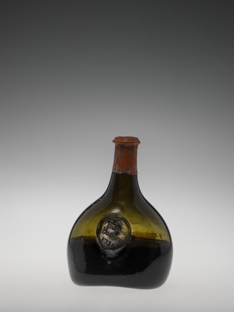 Wine bottle, England, 1730. Non lead Glass, Liquid Wine, Lead, Foil, Paint. Overall H: 18.5 cm; Base W: 10.5 cm. 68.2.11