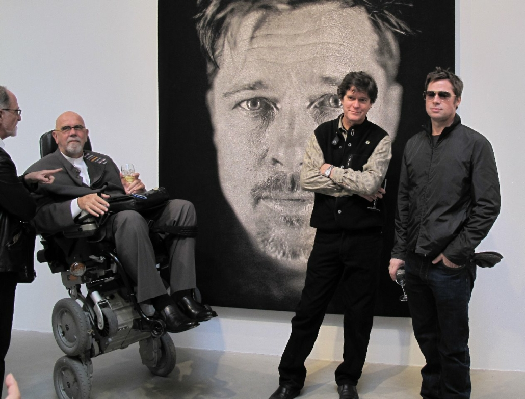 Artist Chuck Close, second from left, in 2009 at the PaceWildenstein gallery debut of his tapestry portrait of actor Brad Pitt. Close died August 19 at the age of 81. Also pictured, left to right, are Michael Danoff, Donald Farnsworth and Pitt. Image courtesy of Wikimedia Commons and Sotolux, shared under the Creative Commons Attribution 3.0 Unported license.