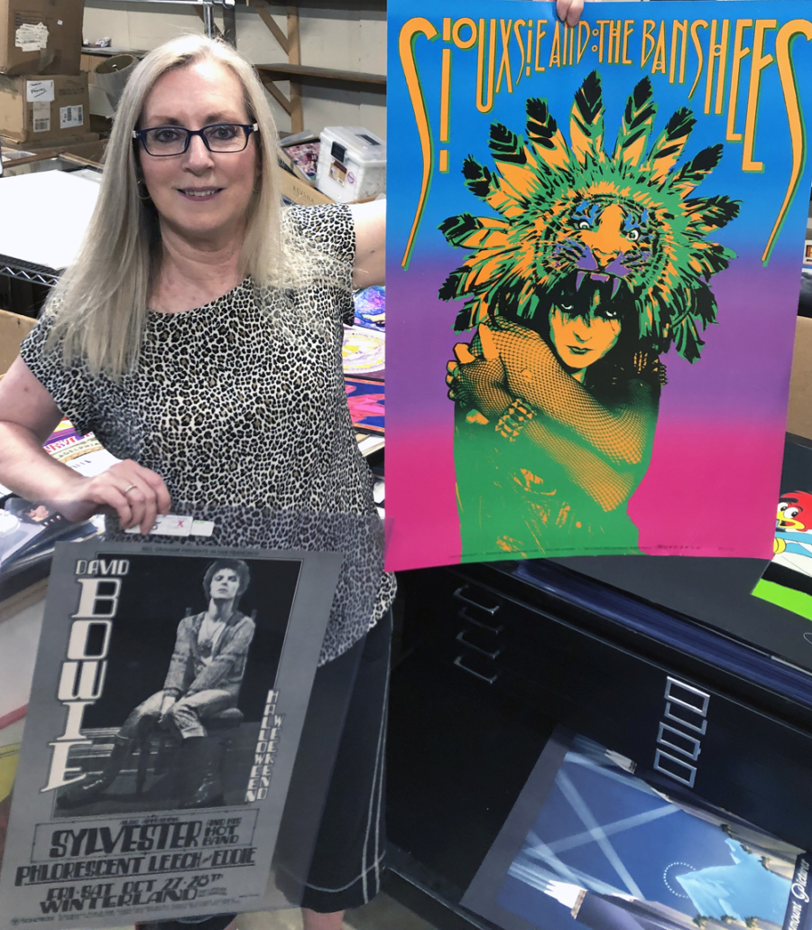 Ranking high among Cindy Stephenson's all-time most fun auctions was selling rock concert posters from the estate of Perry Pfeffer in August 2020. Here, she shows off two posters that were offered in that sale. Photo courtesy of Stephenson's Auction.
