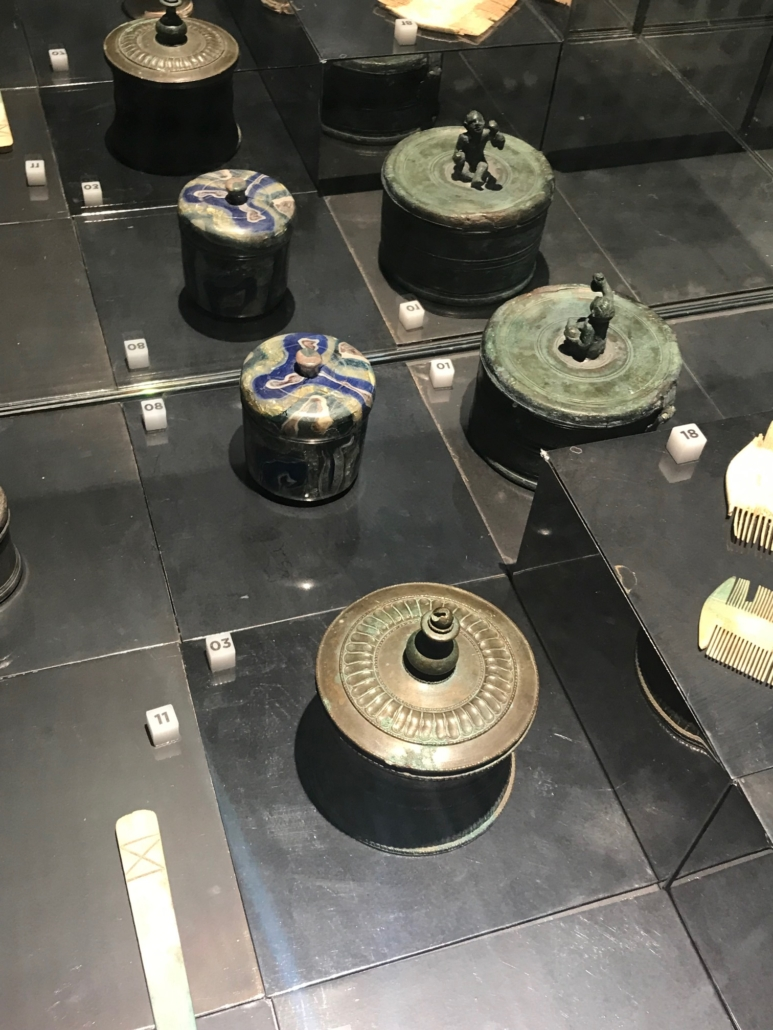 A display in the Palestra Grande showcases small metal containers with lids and decorative finials. Photo credit Andrea Valluzzo